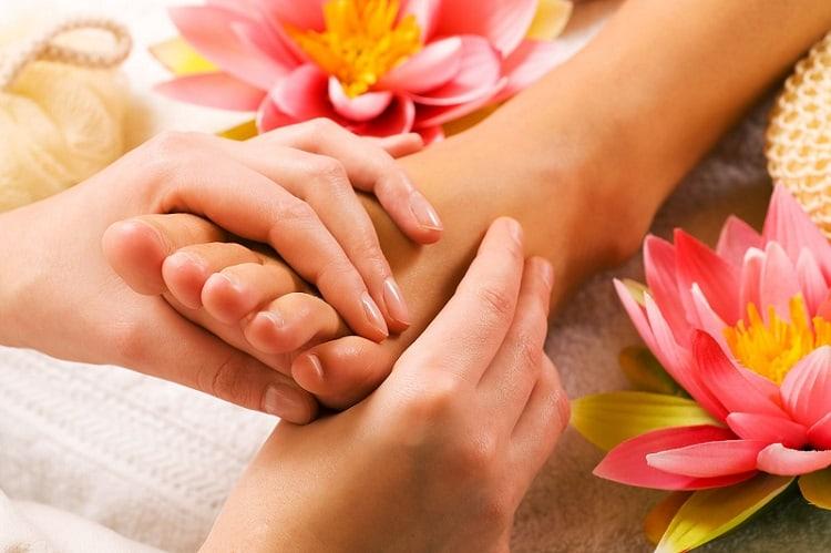 example of reflexology massage, feet massage with flowers surrounding the feet